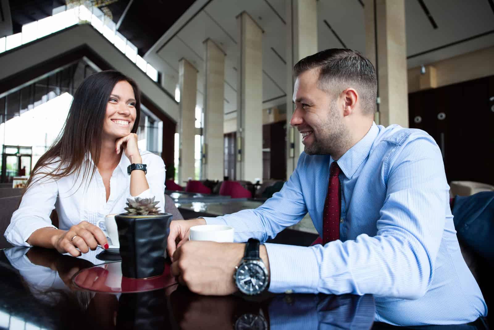 un homme et une femme assis à une table en riant