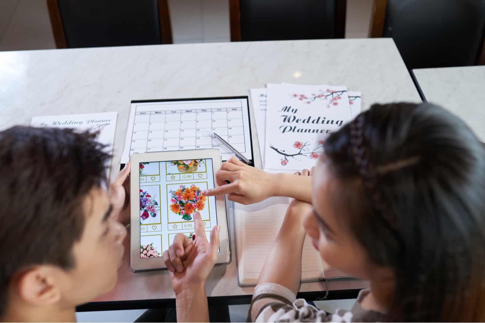 un homme et une femme écrivent des organisateurs de mariage