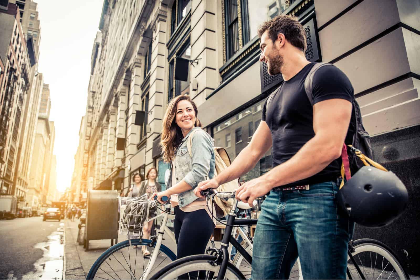 un homme et une femme font du vélo l'un à côté de l'autre et rient