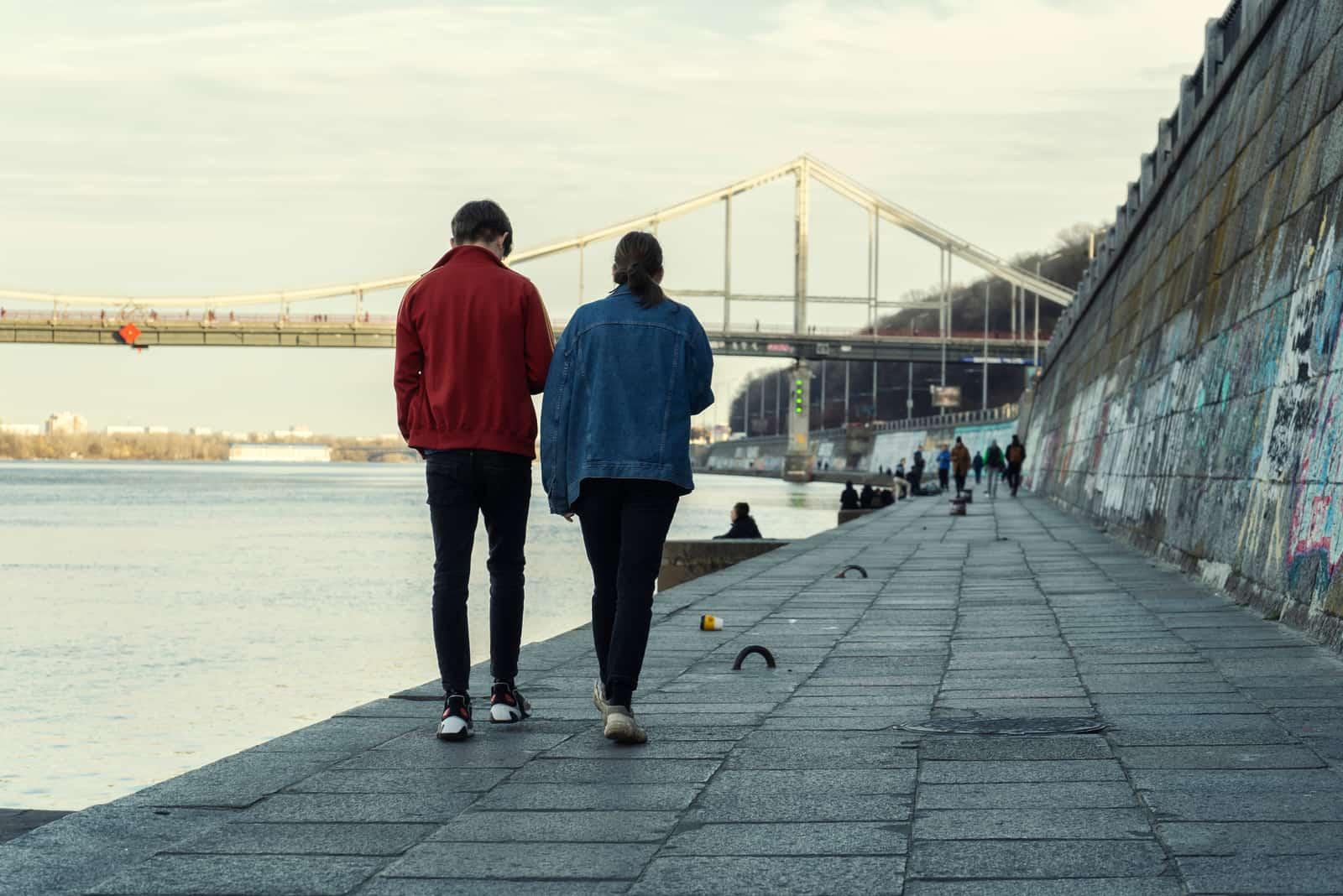 un homme et une femme marchent le long du rivage