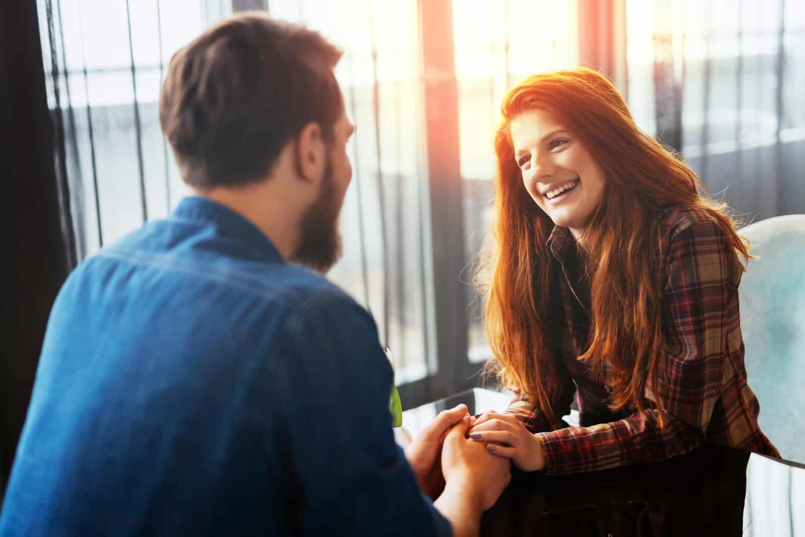 un homme et une femme parlent en se tenant la main
