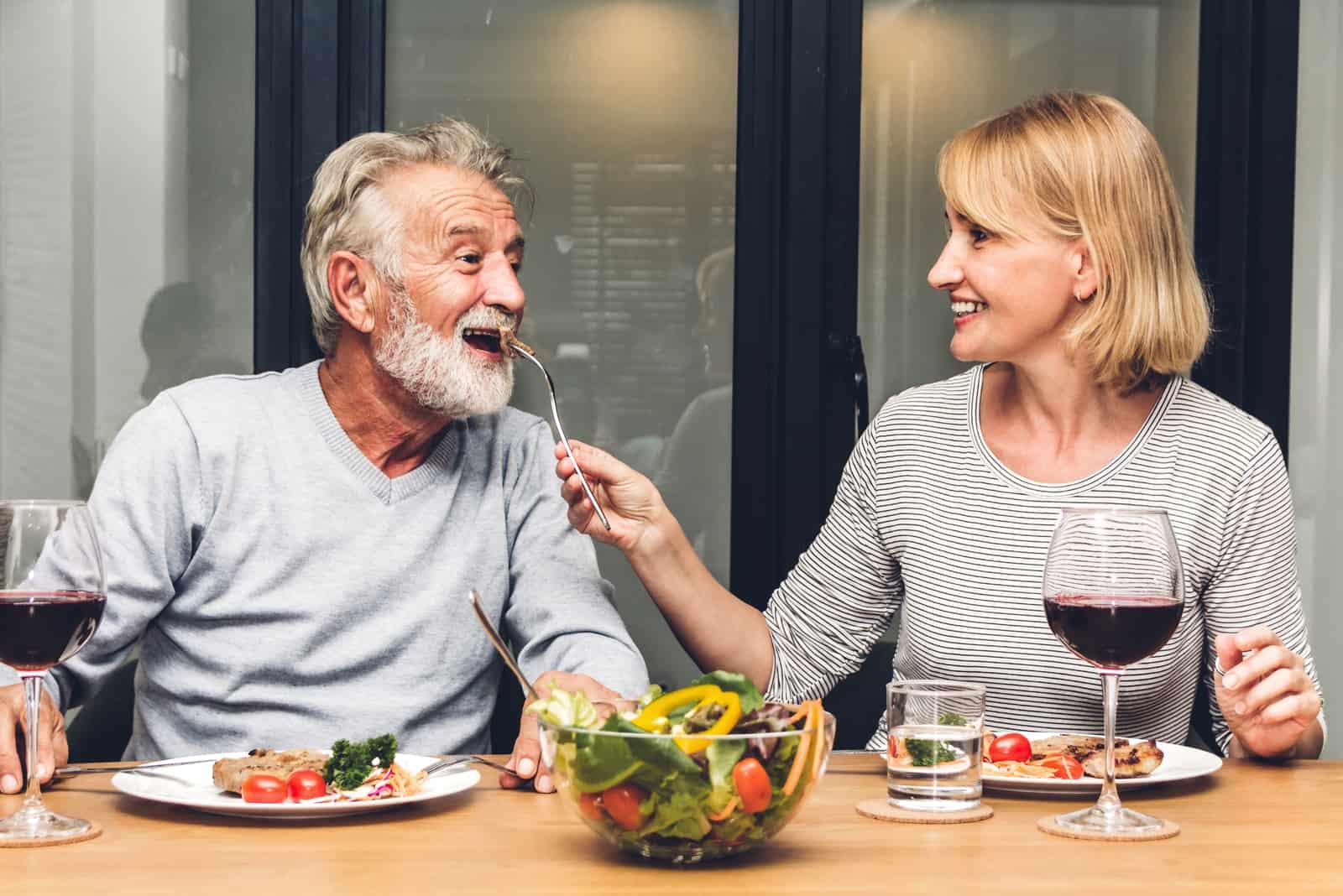 un homme et une femme plus âgés mangent à la maison
