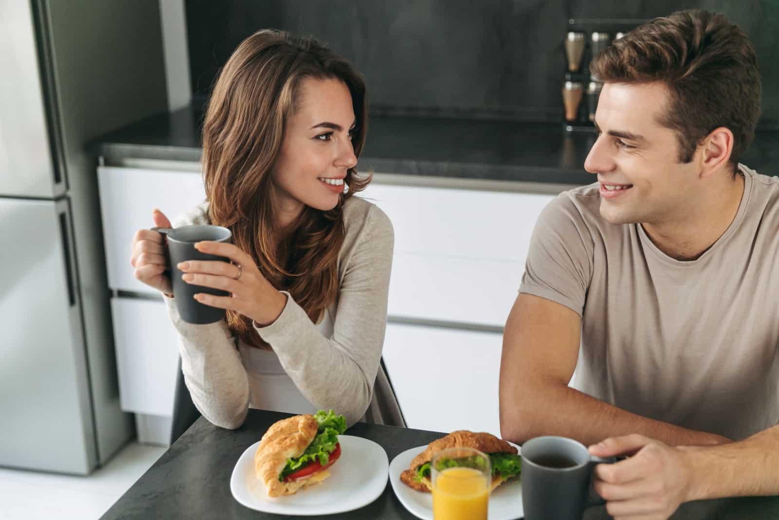un homme et une femme prennent le petit déjeuner et discutent