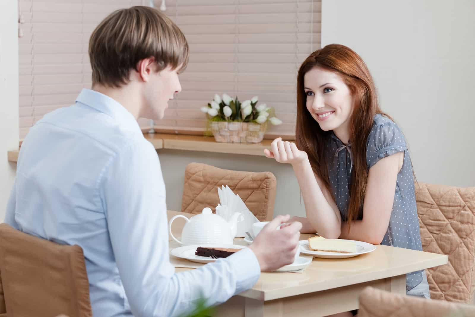 un homme et une femme s'assoient face à face et parlent
