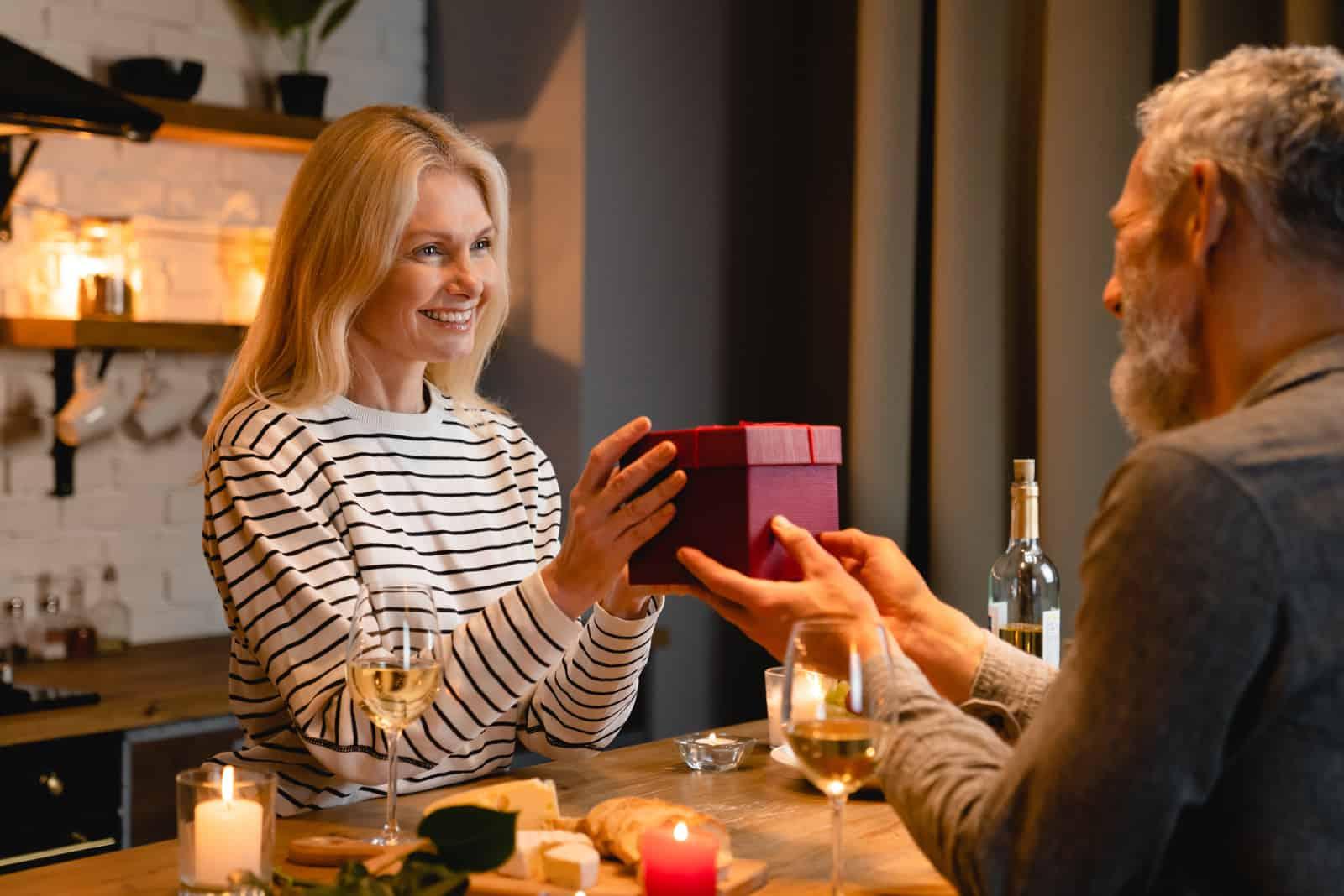 un homme et une femme s'assoient pour dîner il lui fait un cadeau
