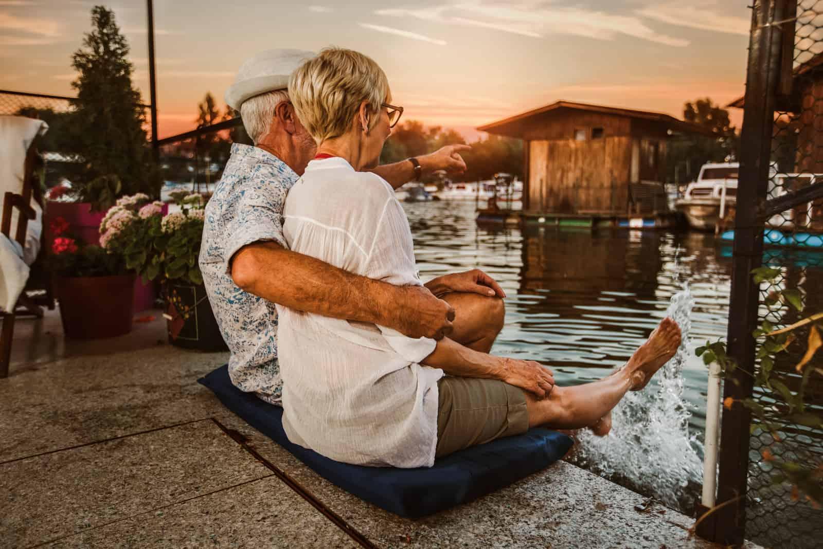 un homme et une femme s'assoient sur la jetée et regardent le coucher du soleil
