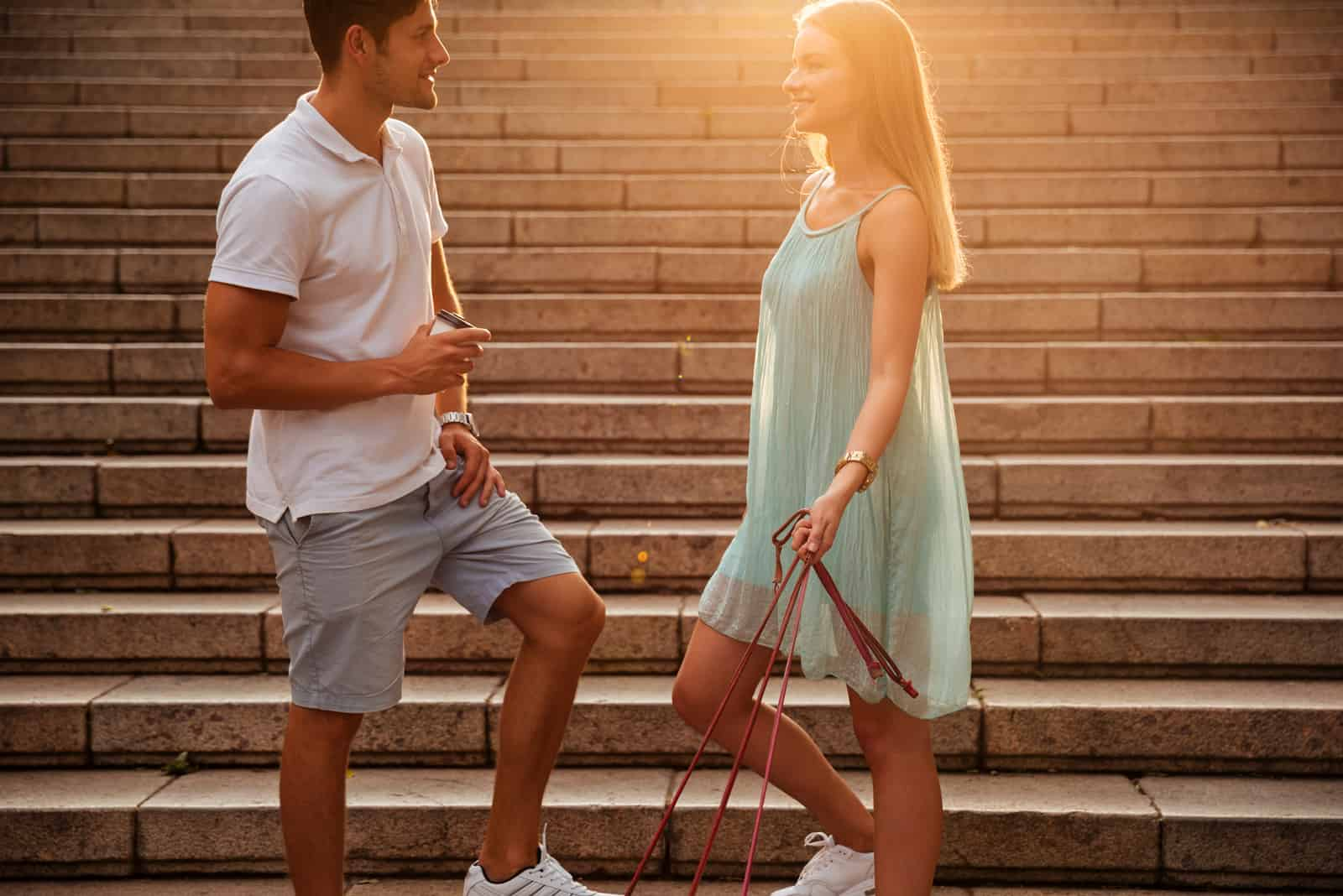 un homme et une femme se tiennent dans les escaliers et parlent