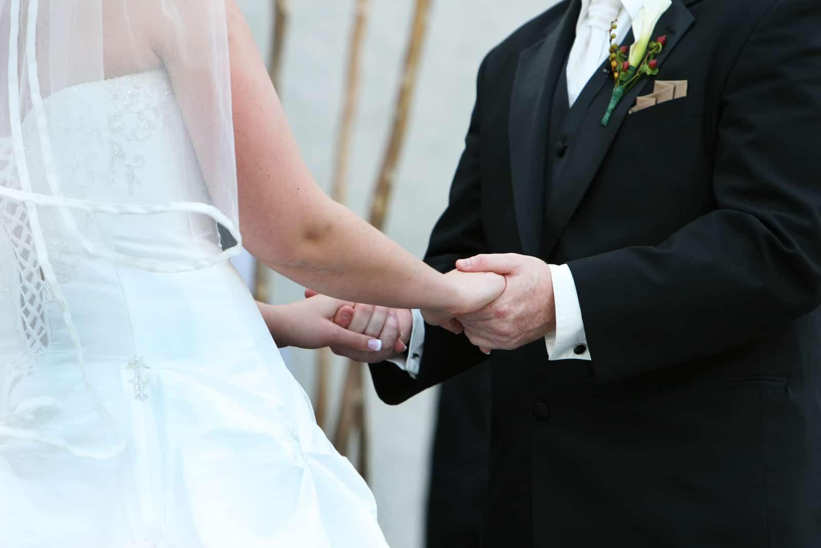 un homme et une femme se tiennent la main lors d'un mariage