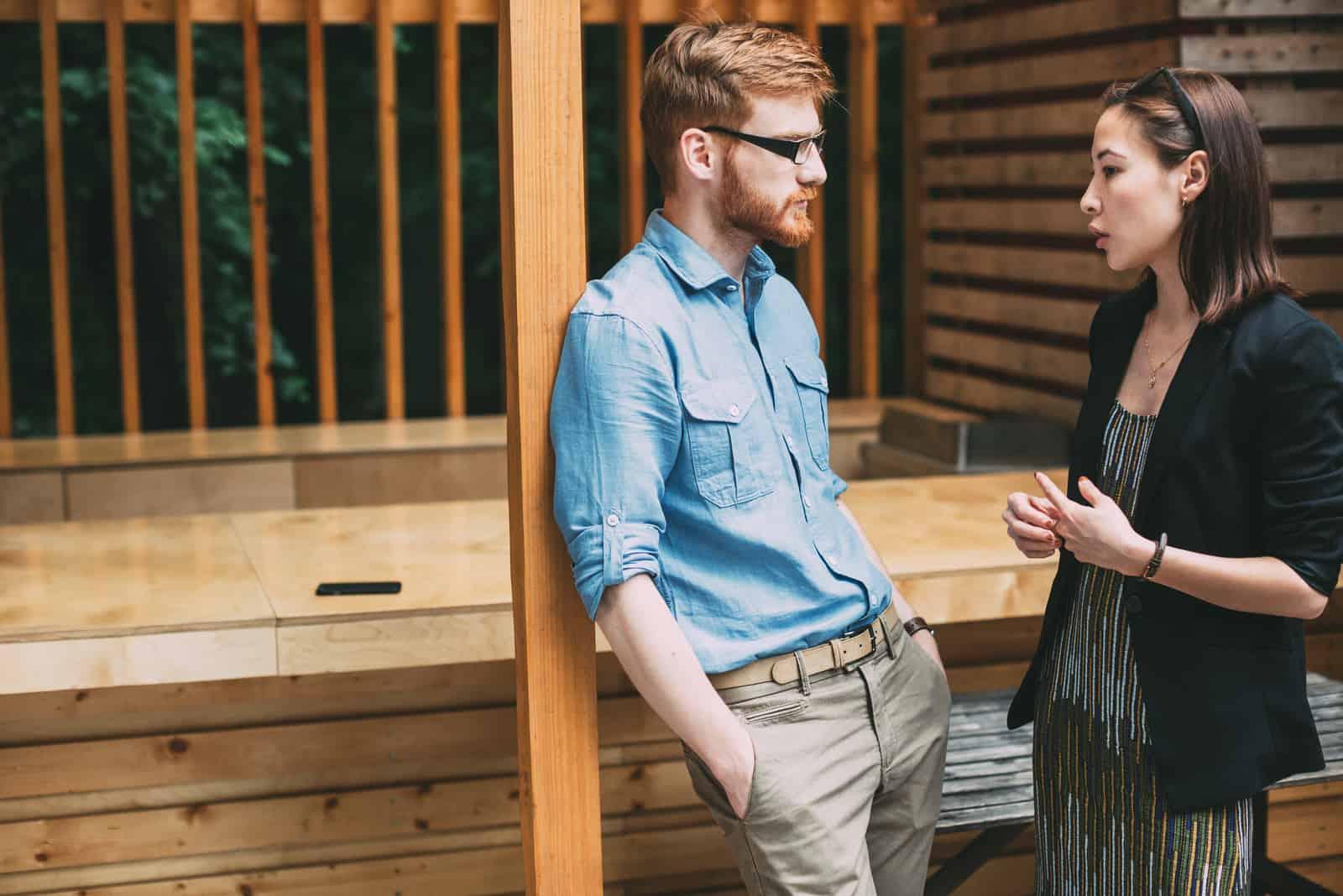 un homme et une femme se tiennent près de la fenêtre et parlent