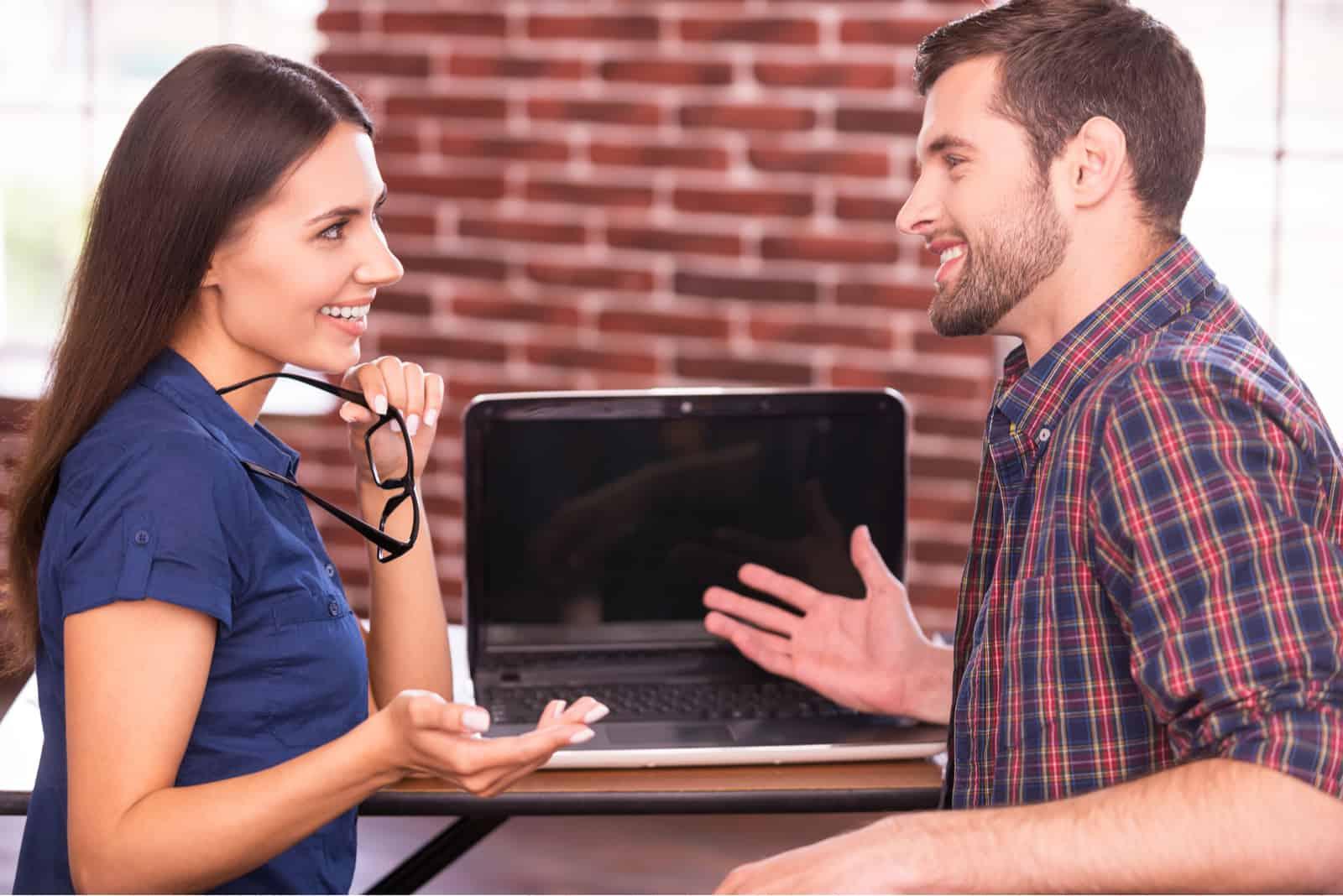 un homme et une femme sont assis à une table et parlent