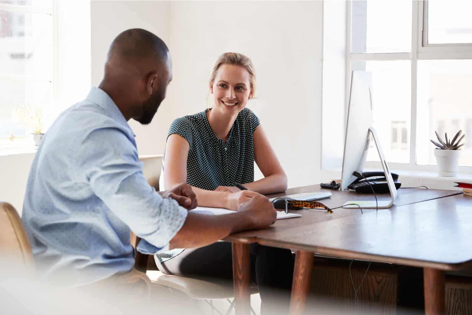 un homme et une femme sont assis au bureau et parlent