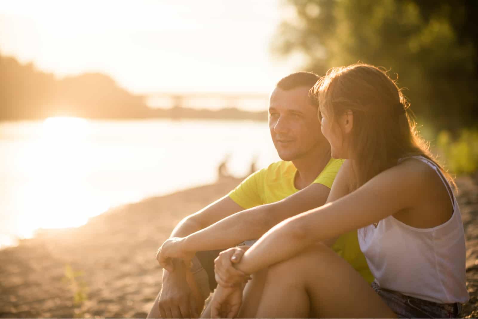 un homme et une femme sont assis et parlent sur la plage