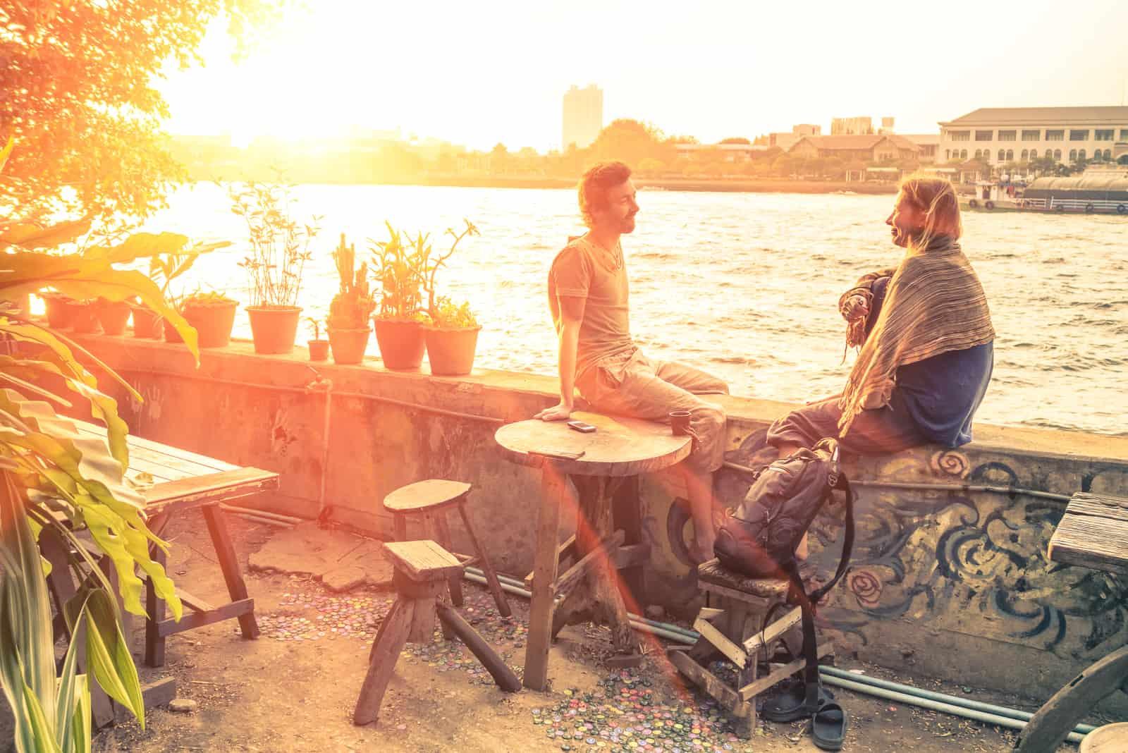 un homme et une femme sont assis sur un mur au bord de la mer et rient