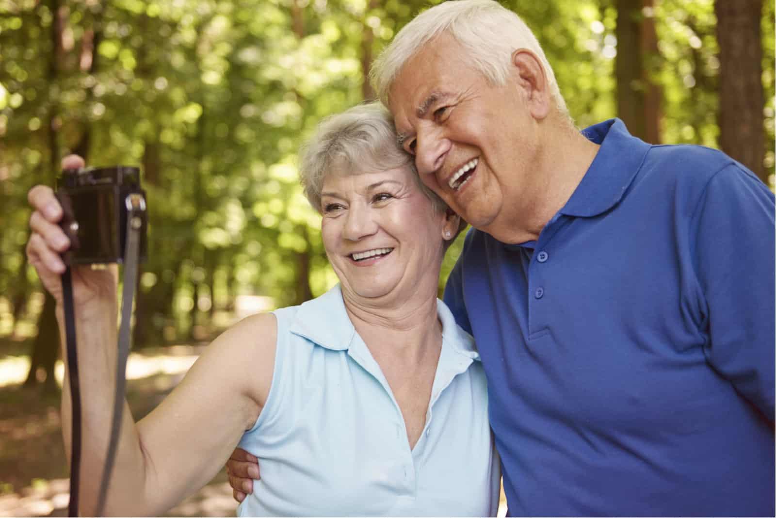 un homme et une femme souriants prennent des photos