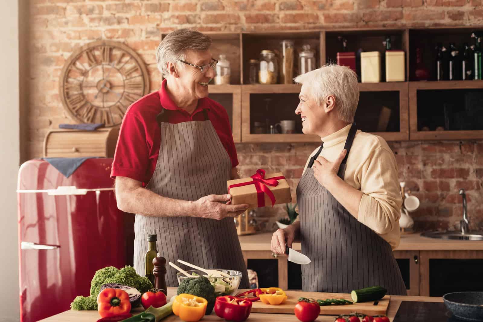 un homme offre un cadeau à une femme pendant qu'elle se tient dans la cuisine et cuisine
