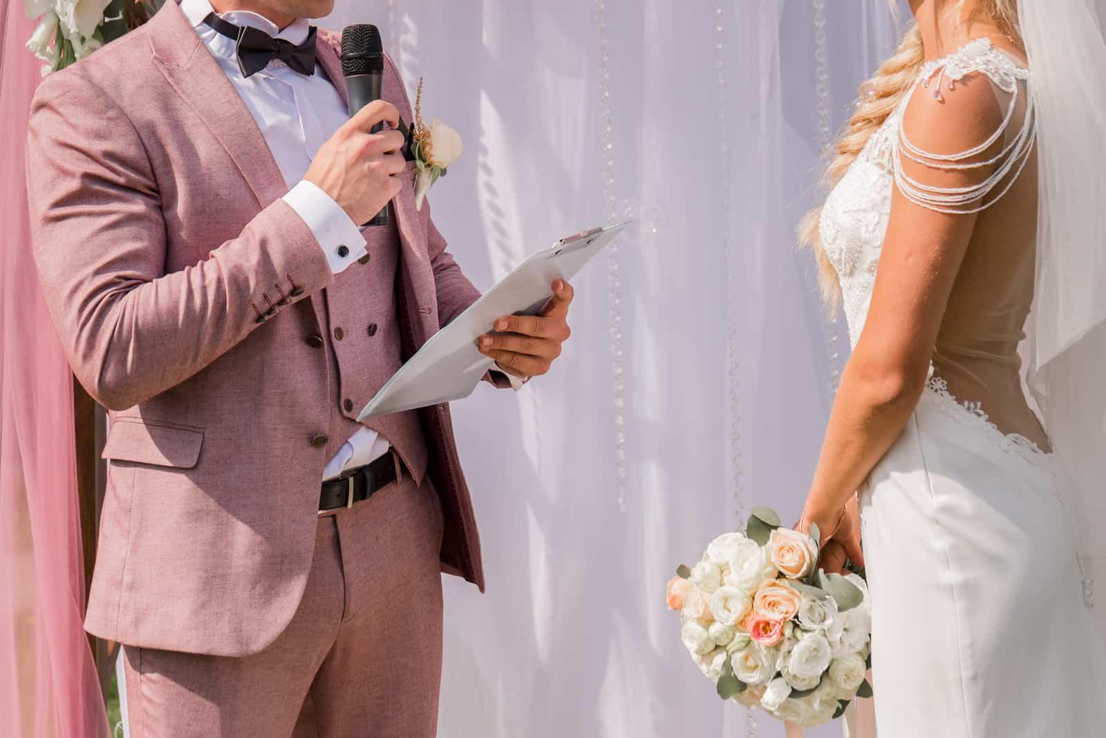un homme parle dans un micro lors d'un mariage