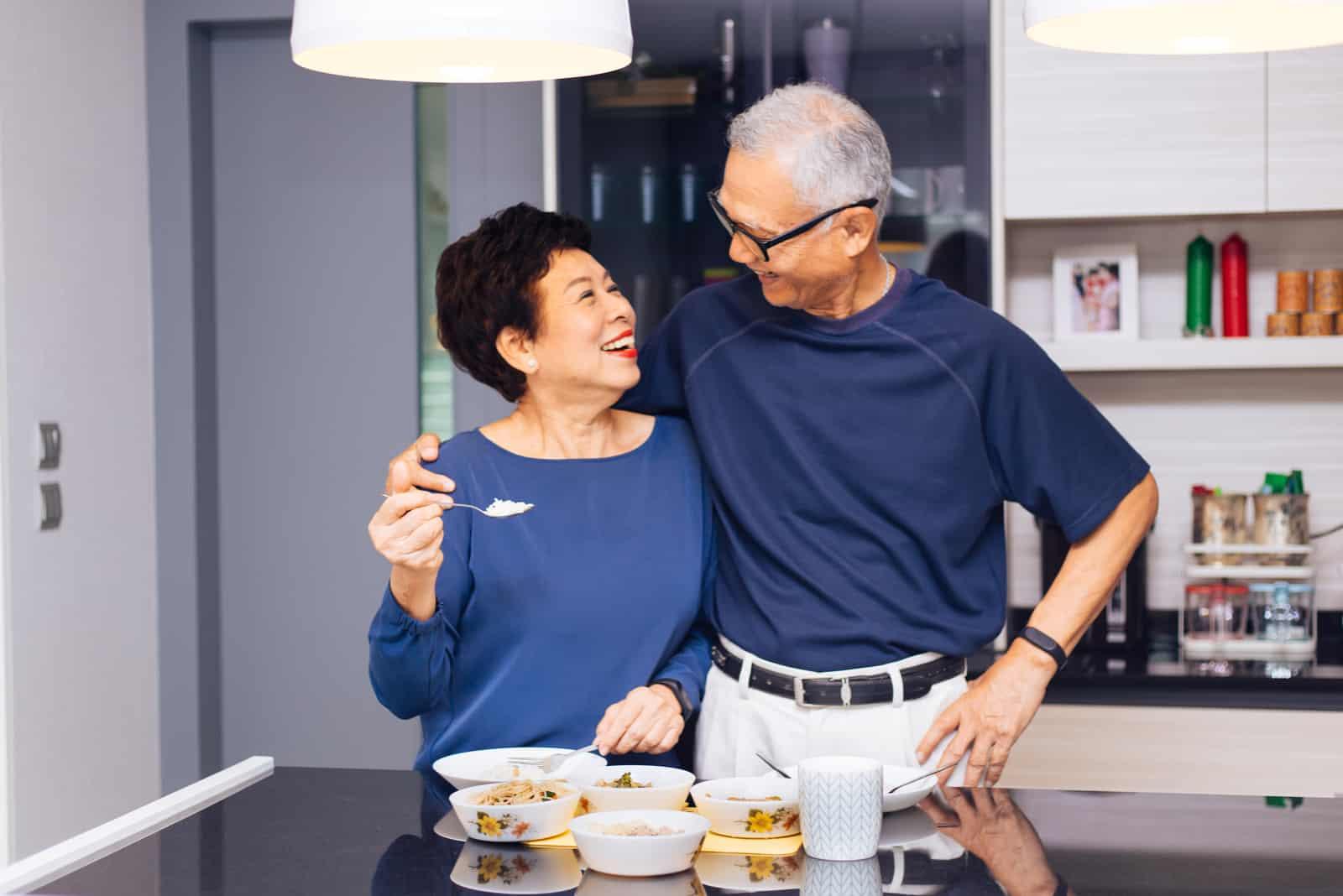 un homme souriant a embrassé la femme dans la cuisine