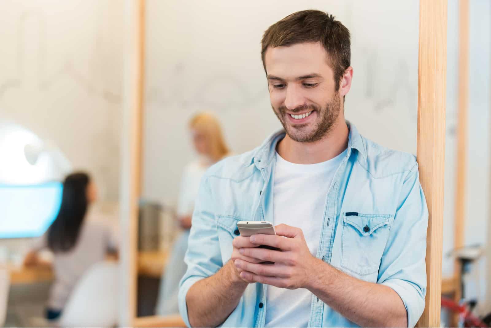 un homme souriant debout appuyé contre un mur et appuyant sur un bouton du téléphone