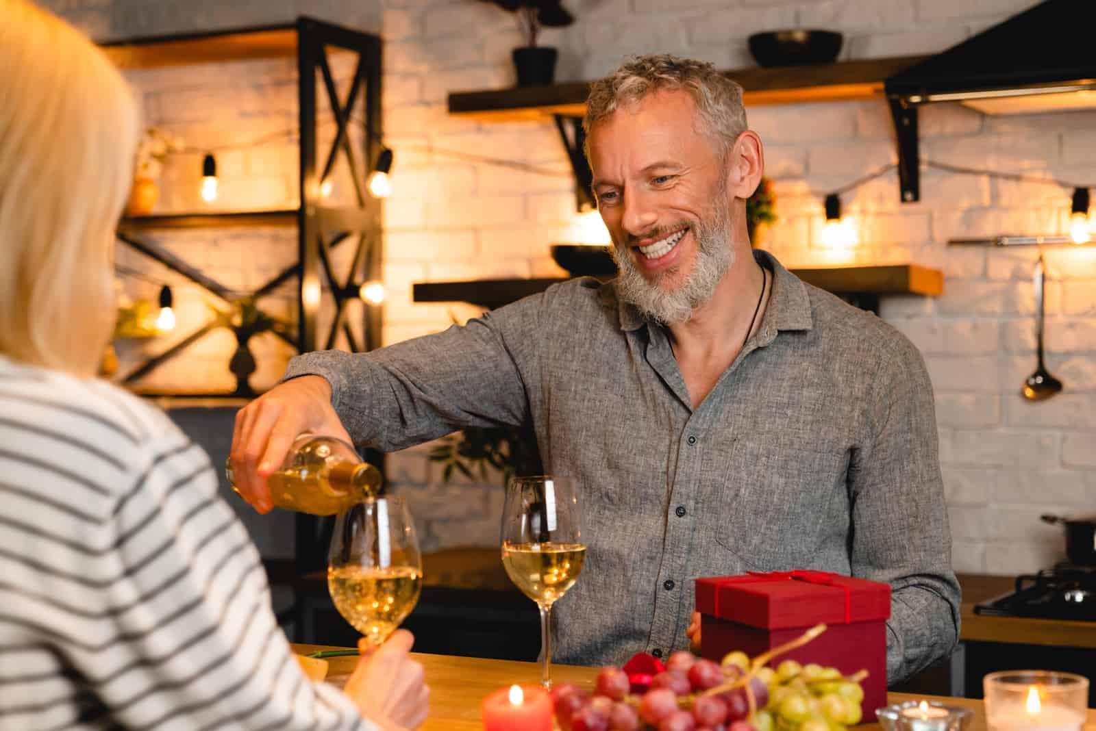 un homme verse du vin assis avec une femme au dîner