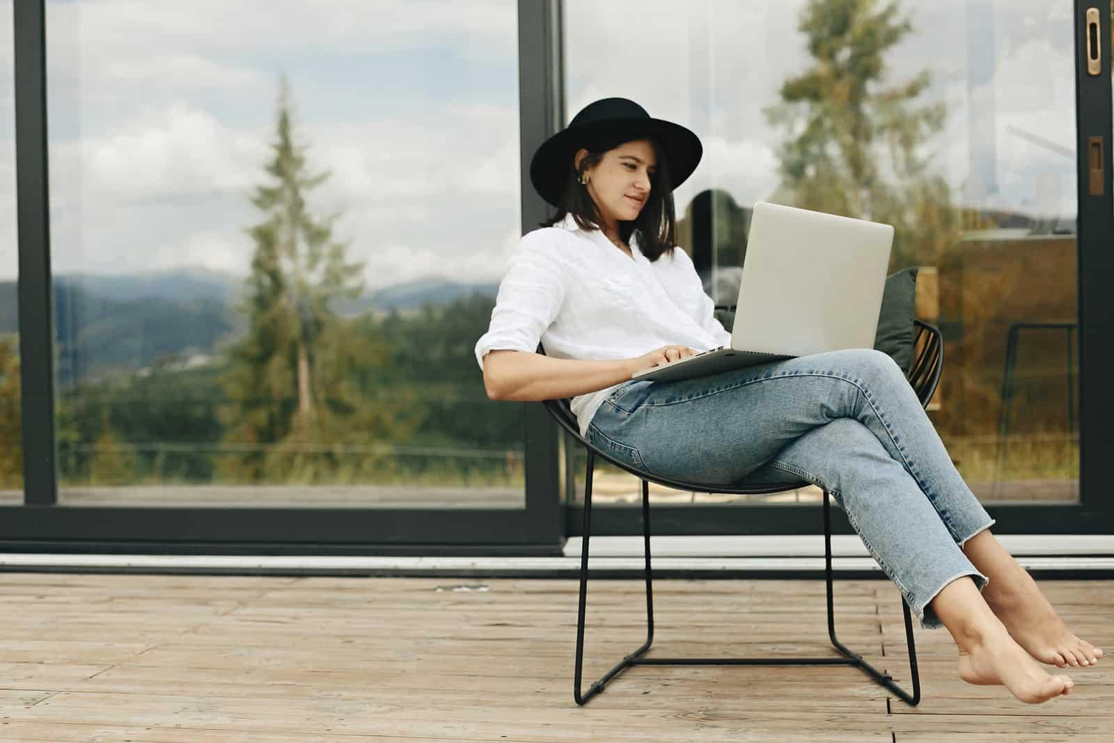 une belle femme assise sur une chaise avec une tablette sur ses genoux