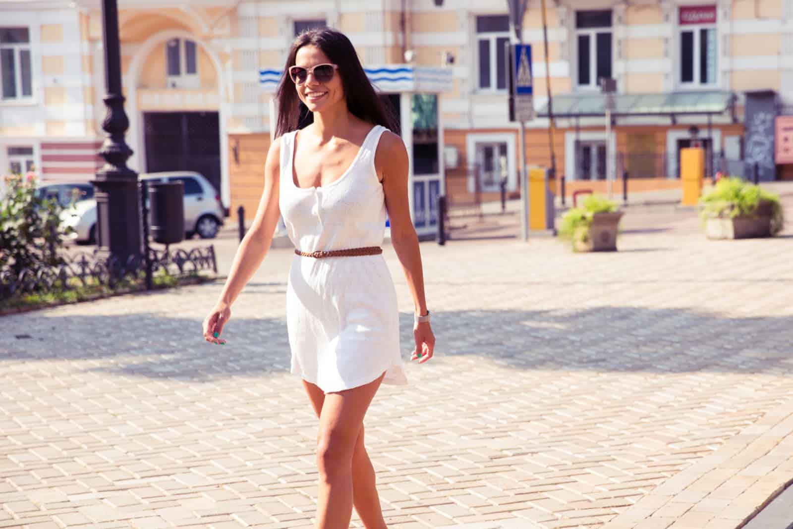 une belle femme vêtue d'une robe blanche marche dans la rue