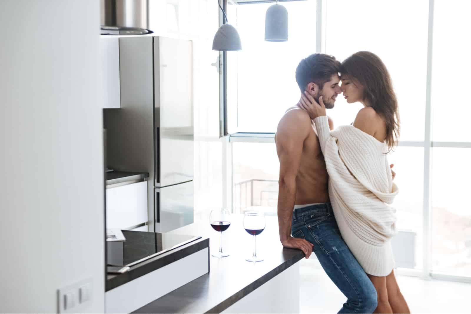 une femme à moitié nue étreint un homme dans la cuisine