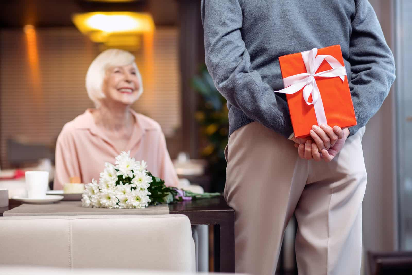 une femme assise à une table un homme veut la surprendre avec un cadeau