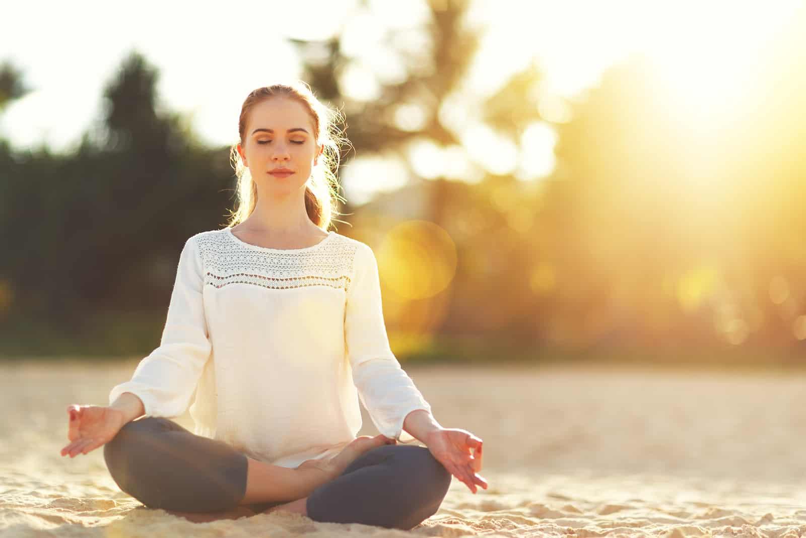 une femme assise sur la plage et méditant