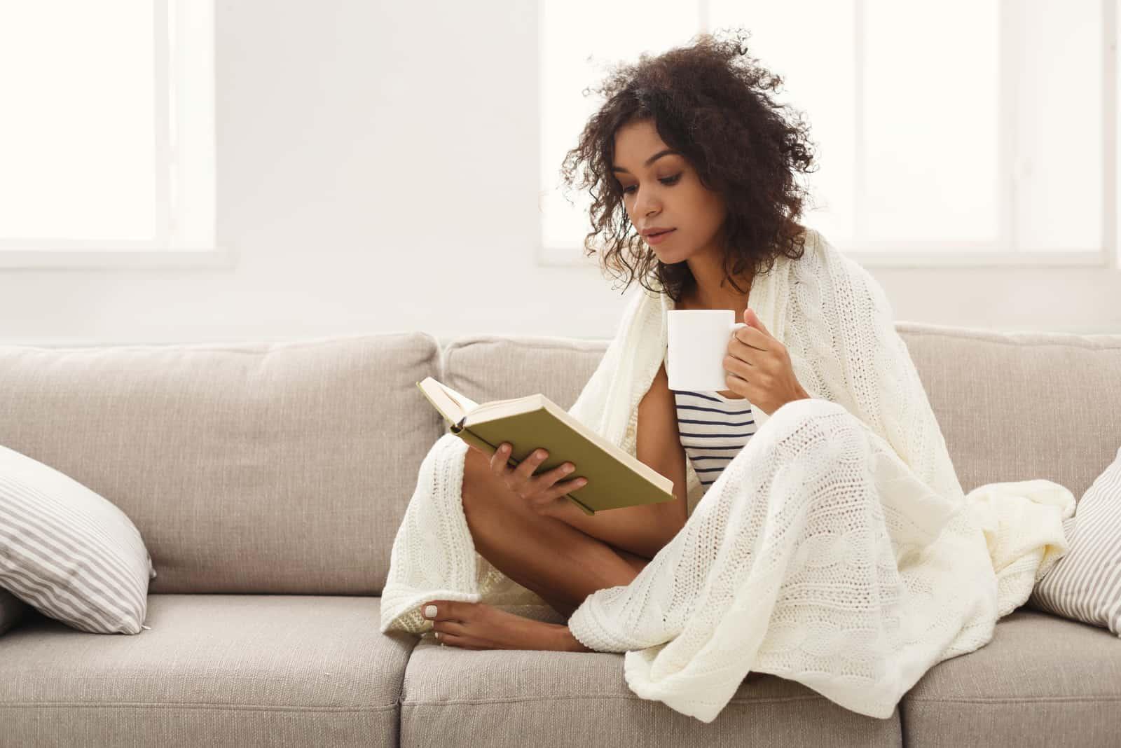 une femme aux cheveux crépus est assise sur le canapé en train de boire du café et de lire