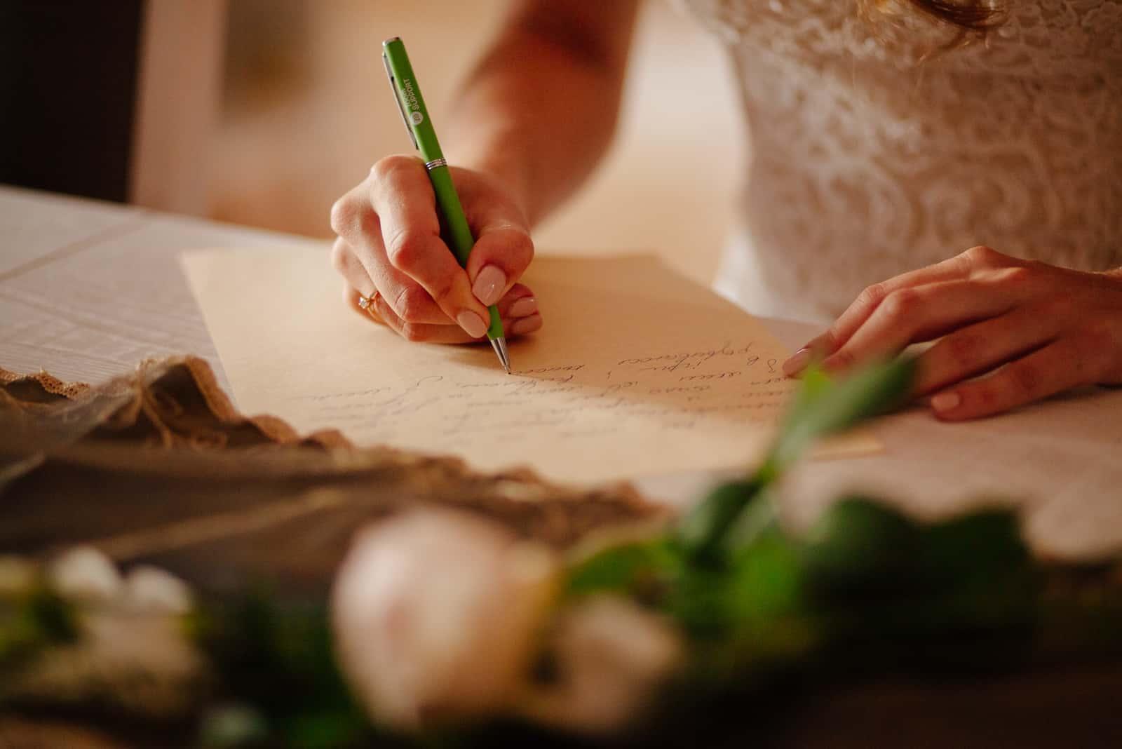 une femme est assise à une table et écrit des vœux