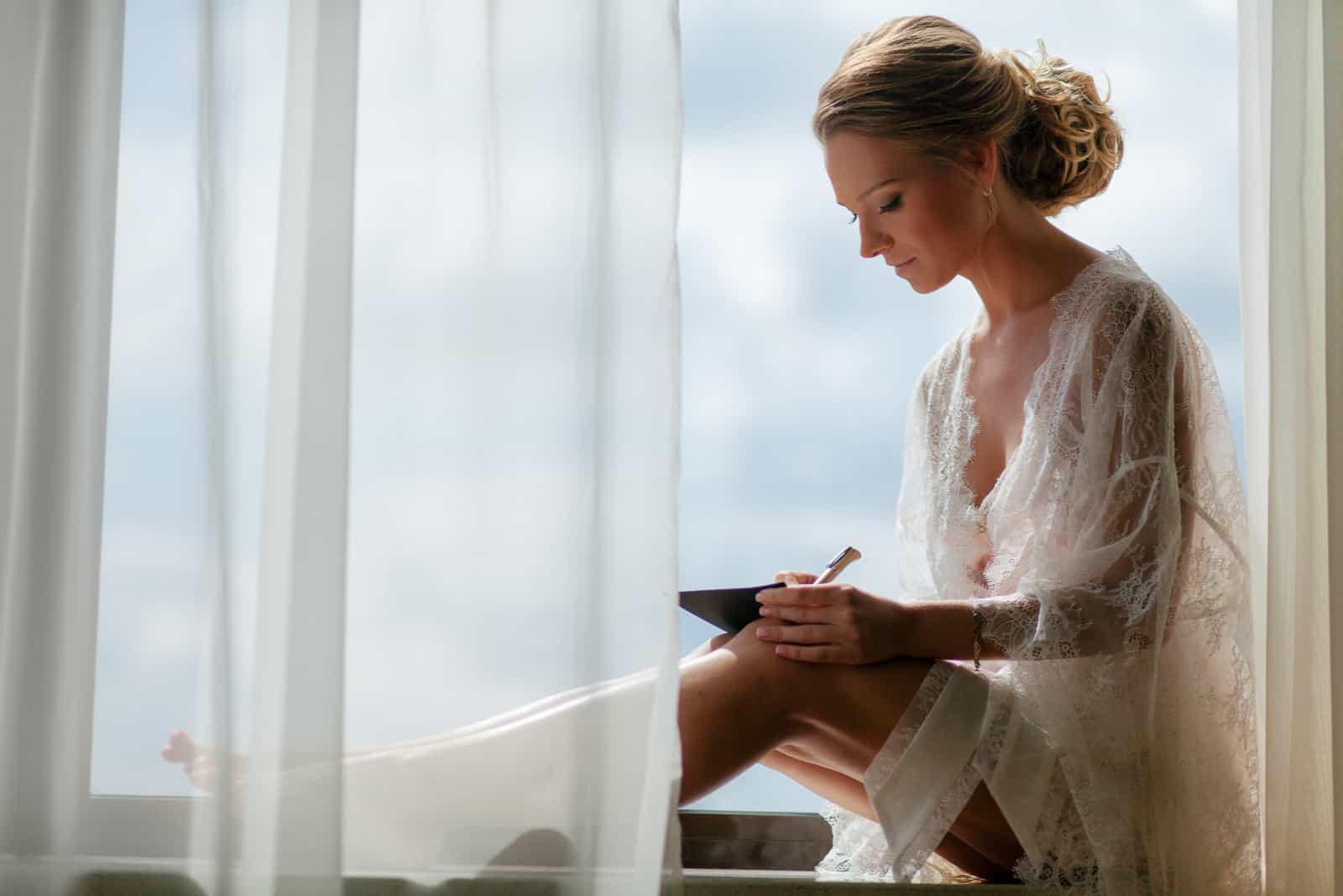 une femme est assise près de la fenêtre et écrit des vœux