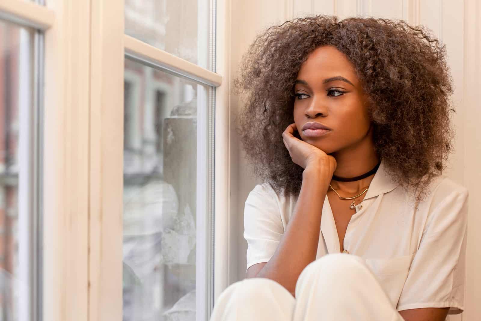 une femme imaginaire aux cheveux crépus est assise et regarde par la fenêtre