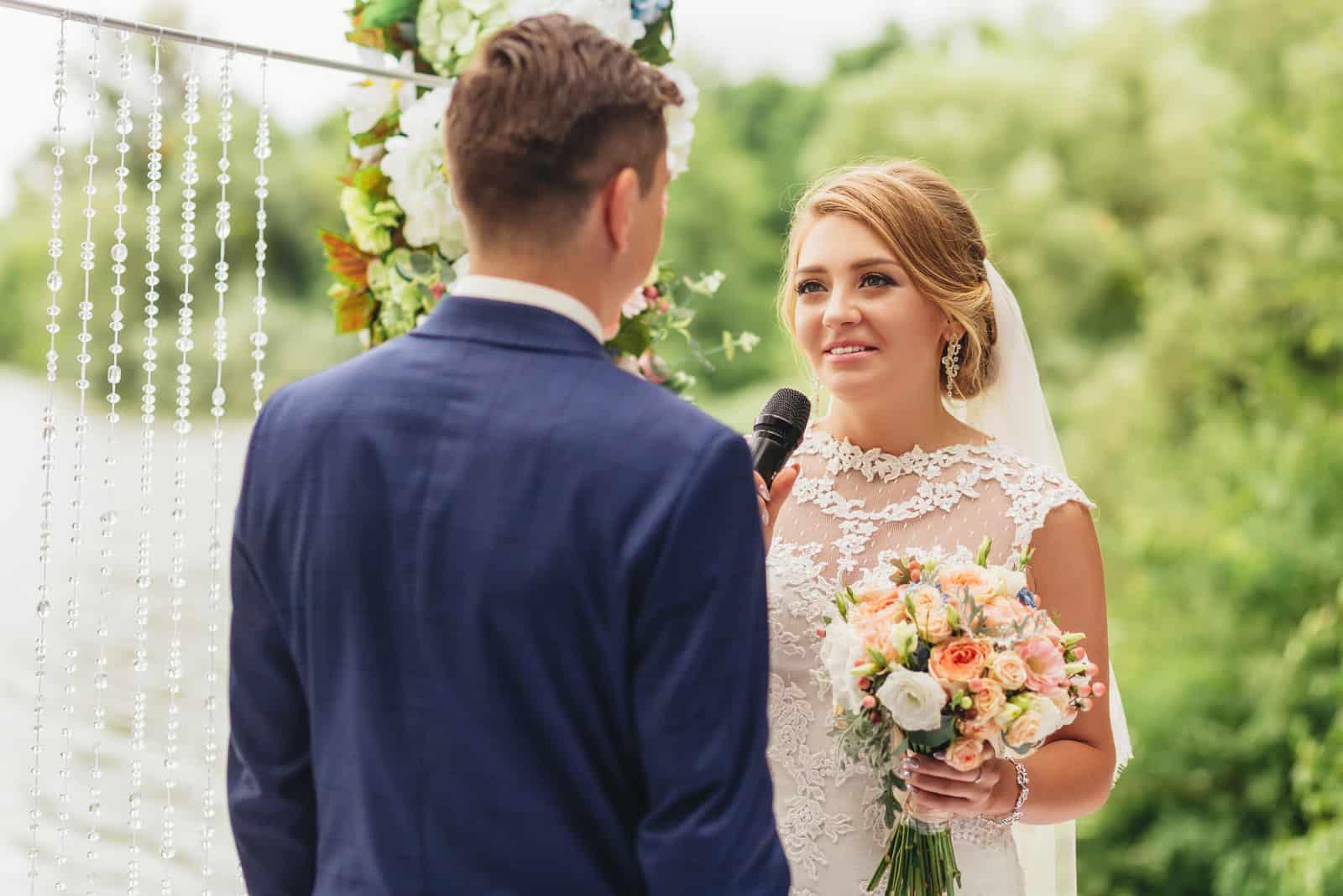 une femme parle dans un micro lors d'un mariage