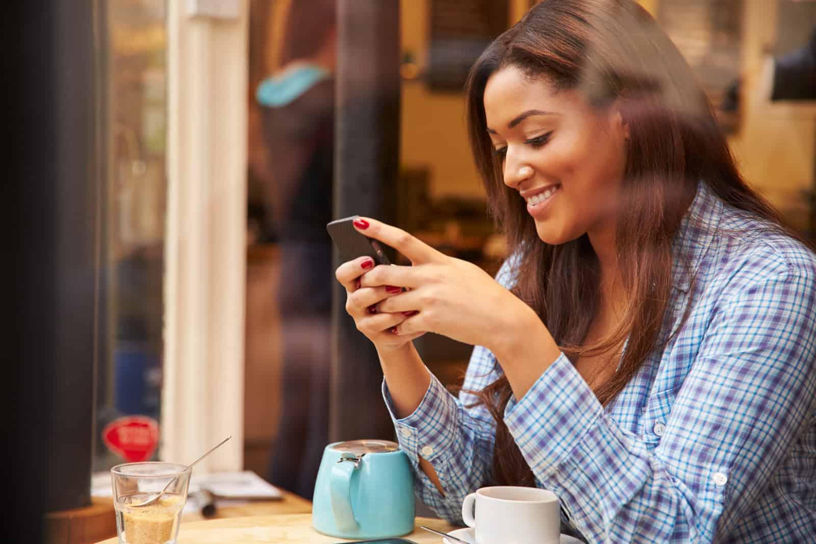 une femme souriante assise dans un café et tapant au téléphone