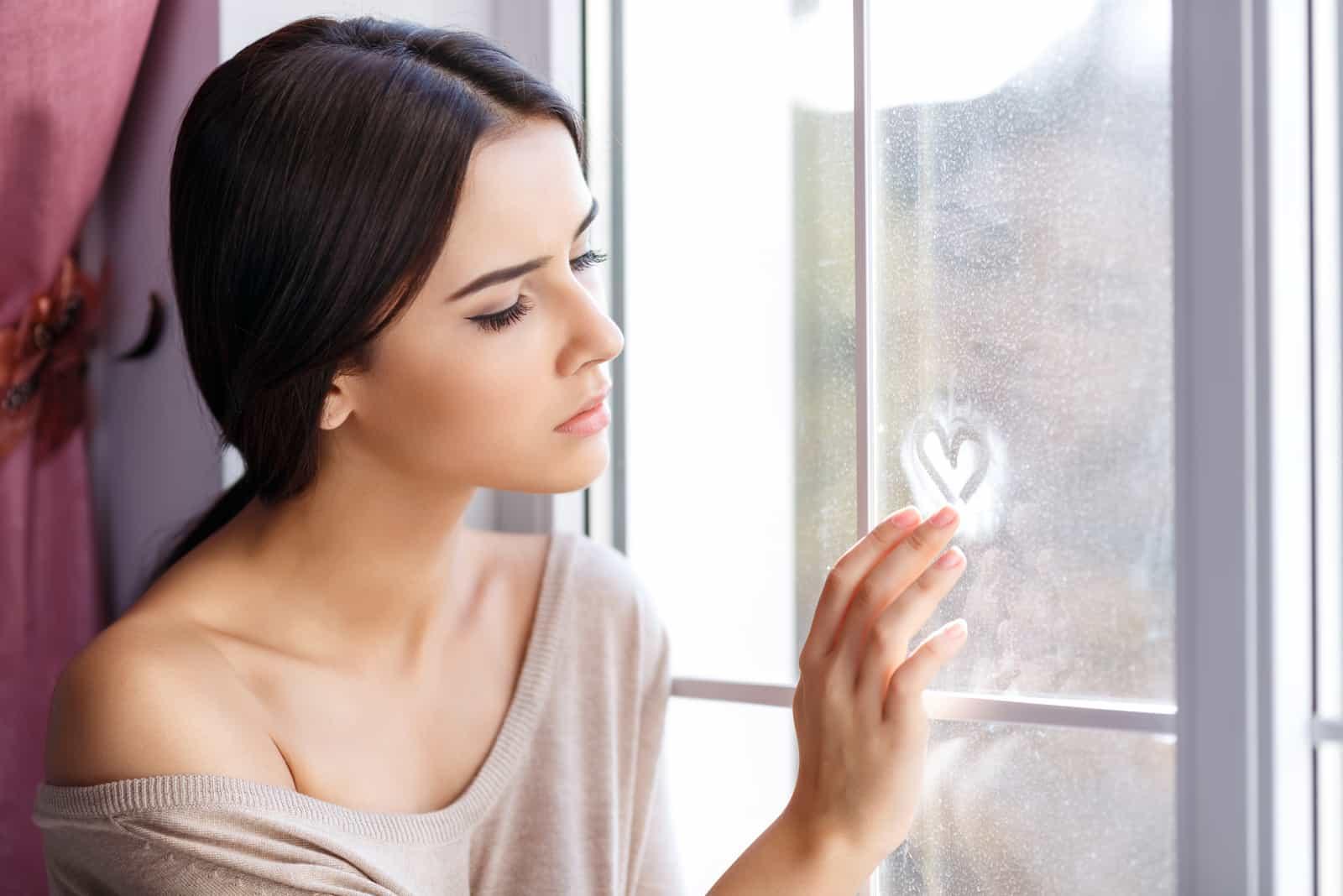 une femme triste dessine un coeur sur la fenêtre
