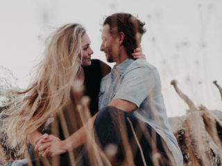 homme et femme se tenant la main assis dans un champ