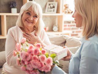 la fille a surpris sa mère avec un bouquet de roses et un cadeau