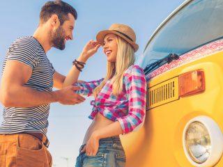 un homme et une femme souriants se tiennent près du bus et parlent