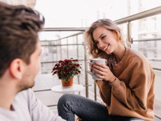 un homme et une femme s'assoient sur le balcon et rient