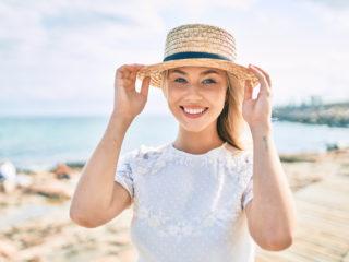 une femme souriante se tient avec un chapeau sur la tête