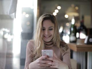 Femme heureuse utilisant un smartphone alors qu'elle est assise dans un café
