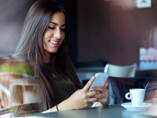 une belle femme aux longs cheveux noirs est assise à côté d'un bouton de café au téléphone