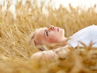 une femme aux cheveux blonds se trouve dans un champ de blé