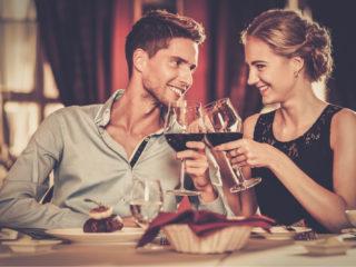 un homme et une femme trinquent avec un verre au dîner
