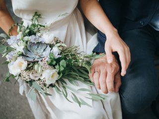 un homme et une femme s'assoient et tiennent un bouquet à la main