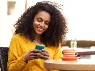 une femme souriante aux cheveux crépus assise à une table et tapant sur un téléphone