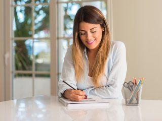 une femme souriante est assise en train d'écrire