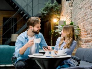 un homme et une femme sont assis dans un café et boivent du café