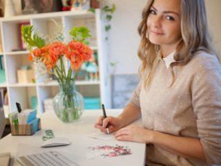 une femme aux cheveux blonds souriante est assise à une table et écrit