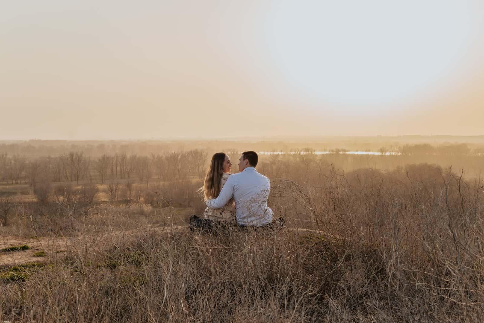 homme et femme s'embrassant assis dans un champ